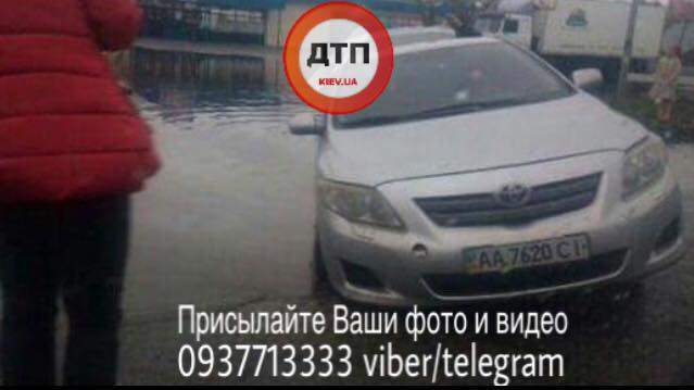В Киеве на выезде с парковки автомобиль провалился в глубокую яму (Фото)
