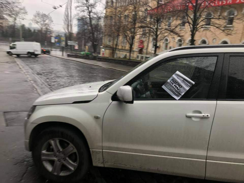 """Неизвестные в Киеве прямо на автомобили клеили """"приглашения"""